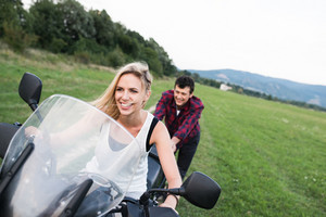 Beautiful young couple in love enjoying a motorbike ride in countryside. Man pushing woman sitting on motorcycle.