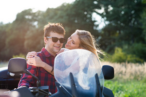 Beautiful young couple in love enjoying a motorbike ride in countryside.