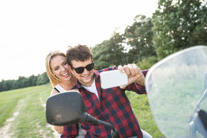 Beautiful young couple in love enjoying a quad bike ride in countryside. Couple driving off-road with ATV. Taking selfie with smart phone.