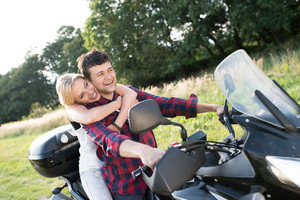 Beautiful young couple in love enjoying a quad bike ride in countryside. Couple driving off-road with ATV.