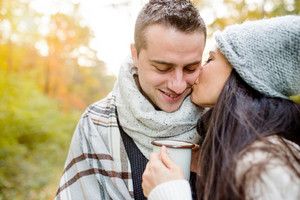 Beautiful young couple in love hugging and kissing. Sunny autumn forest.
