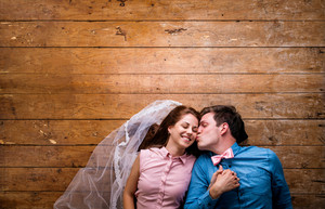 Beautiful young couple in love hugging, kissing, lying on a floor. Woman with veil, man with bow tie. Studio shot on wooden background. Copy space.