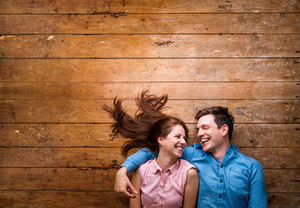 Beautiful young couple in love hugging, lying on a floor. Studio shot on wooden background. Copy space.