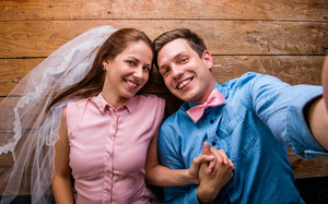 Beautiful young couple in love hugging, lying on a floor, taking selfie. Woman with veil, man with bow tie. Studio shot on wooden background.