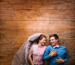 Beautiful young couple in love hugging, lying on a floor. Woman with veil, man with bow tie. Studio shot on wooden background. Copy space.