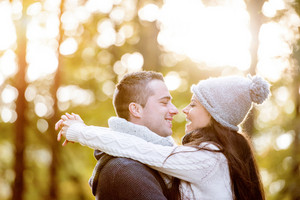 Beautiful young couple in love, hugging. Sunny autumn forest.