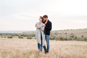 Beautiful young couple in love hugging while standing at the field