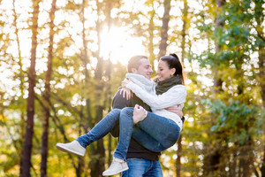 Beautiful young couple in love, man carrying woman in his arms. Autumn forest, sunny day.