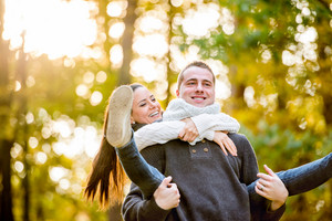 Beautiful young couple in love, man giving his woman piggyback. Autumn forest, sunny day.