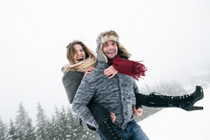Beautiful young couple in love, man giving his woman piggyback. Winter nature, snowy day.