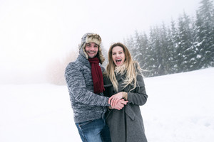 Beautiful young couple in love on a walk in winter nature. Snowy day.