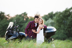 Beautiful young couple in love standing at a motorbike outdoors in green sunny summer nature.