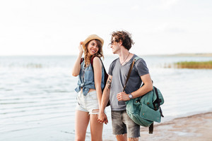 Beautiful young couple in love walking at the beach and looking at each other