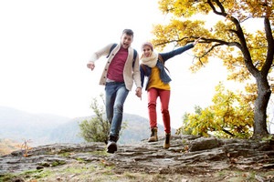Beautiful young couple in sunny autumn nature, running on a rock