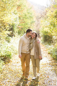 Beautiful young couple in warm clothes on a walk in forest, hugging and kissing. Colorful autumn nature.