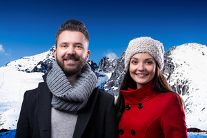 Beautiful young couple in winter clothes standing in front of winter mountains covered with snow