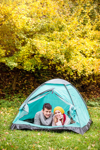 Beautiful young couple lying in tent, camping in autumn nature