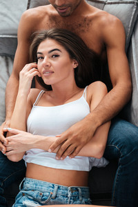Beautiful young couple lying together on couch at home