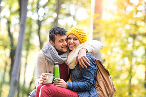 Beautiful young couple on a hike in autumn forest, having tea or coffee in a cup from thermos