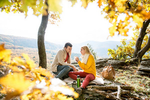 Beautiful young couple on a hike in autumn forest, resting. Eating and having tea or coffee in a cup from thermos. Picnic.