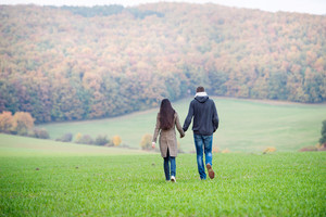 Beautiful young couple on a walk, holding hands. Colorful autumn nature. Rear view.