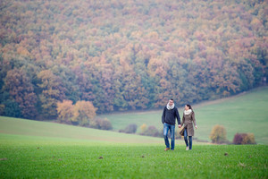Beautiful young couple on a walk, holding hands. Colorful autumn nature.