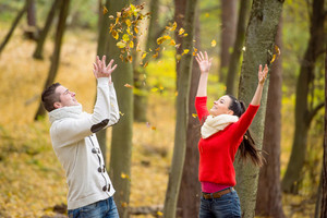 Beautiful young couple on a walk in autumn park throwing leaves