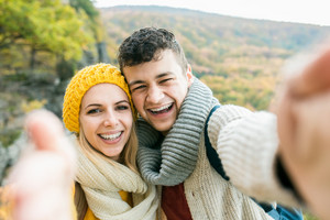 Beautiful young couple on a walk in sunny autumn forest taking selfie