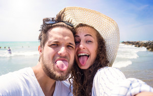 Beautiful young couple on beach, laughing, taking selfie, sticking out tongues. Enjoying time at seaside.