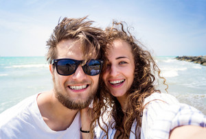 Beautiful young couple on beach, smiling, taking selfie. Enjoying time at seaside.