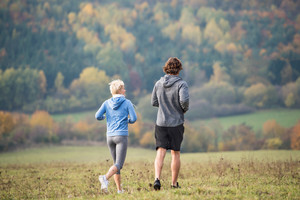 Beautiful young couple running in colorful autumn nature. Close up. Rear view.