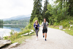 Beautiful young couple running on a path at the lake in green nature.