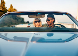 Beautiful young couple sitting and driving cabriolet in summer