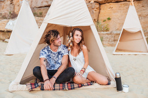 Beautiful young couple sitting in teepee on the beach