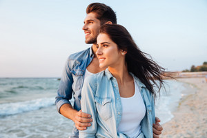Beautiful young couple standing and looking at waves on the beach