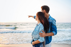 Beautiful young couple standing and pointing away on the beach