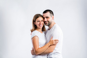 Beautiful young couple. Studio shot on gray background.