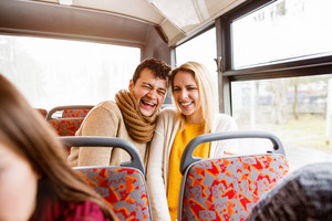Beautiful young couple traveling by bus, laughing, having fun in town.