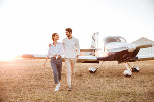 Beautiful young couple walking together across the field with airplane on background at sunset