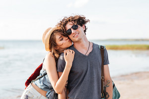Beautiful young couple with backpacks standing and kissing on the beach