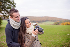 Beautiful young couple with camera taking pictures of sunny autumn nature.