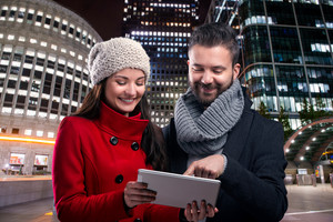 Beautiful young couple with tablet in winter clothes in illuminated night city.
