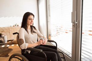 Beautiful young disabled woman in wheelchair at home in her living room, looking out the window, holding a cup of tea or coffee