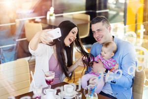 Beautiful young family having fun in cafe