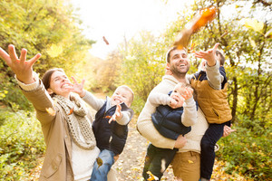 Beautiful young family on a walk in colorful autumn forest. Mother and father carrying their three sons in the arms, throwing leaves in the air.
