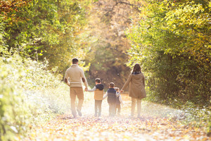 Beautiful young family on a walk in forest. Mother and father with their three sons in warm clothes outside in colorful autumn nature. Rear view.