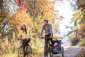 Beautiful young family with baby in jogging stroller cycling outside in autumn nature