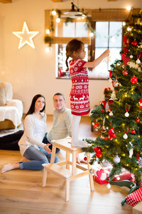 Beautiful young family with little daughter standing on step stool decorating Christmas tree at home.