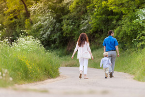 Beautiful young family with little son on a walk on country road in green sunny summer nature. Rear view.