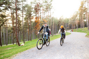 Beautiful young family with two daughters in bicycle seats in warm clothes cycling outside in autumn nature